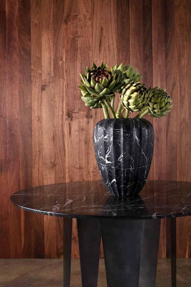 O mármore da mesa encontra similaridade com o vaso de textura idêntica; dentro dele as exuberantes flores de alcachofra