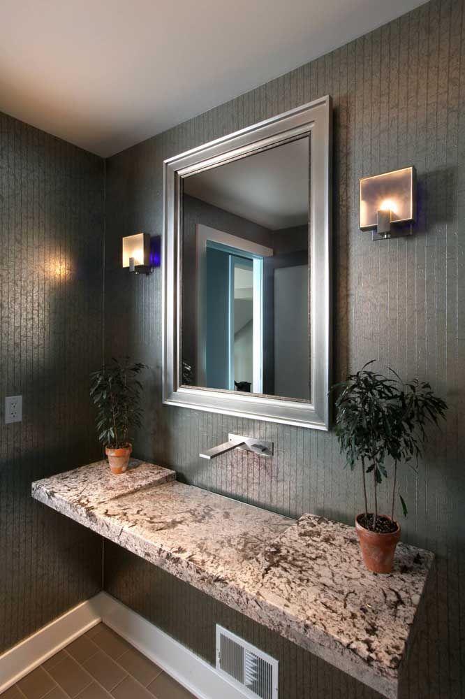 Pia esculpida de granito; para balancear a textura marcante da pedra o restante do banheiro foi planejado em tons neutros