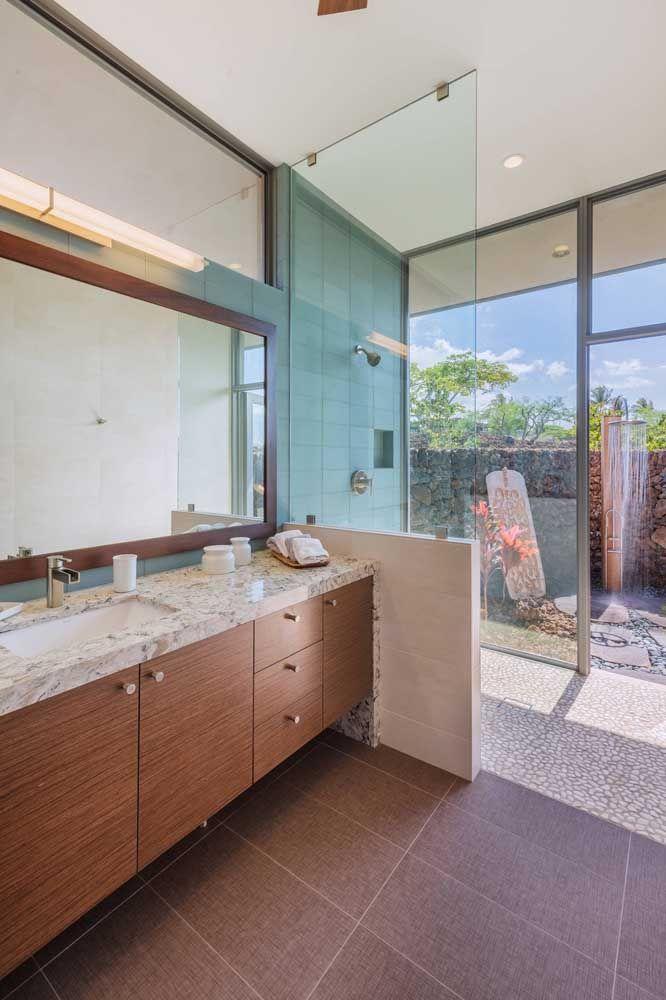 E para quem deseja fugir daqueles banheiros branquinhos pode apostar em móveis de madeira e granito branco