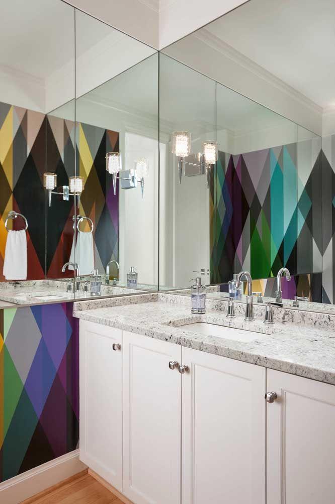 Nesse banheiro, o granito traz a influência clássica e elegante, enquanto a parede colorida mostra o lado moderno e despojado do mesmo projeto