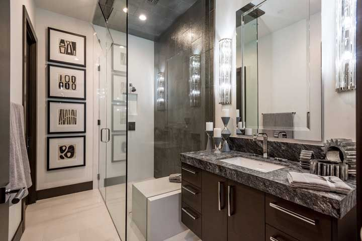 O banheiro de tons marrons não teve medo de encarar um granito preto com granulações brancas