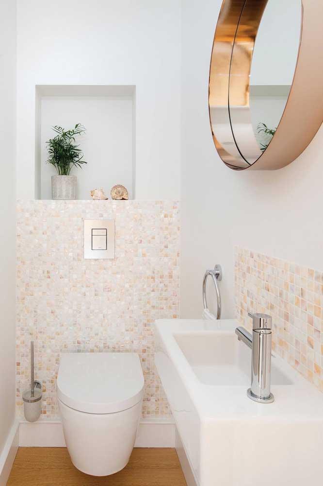 Lavabo decorado com pastilhas que combinam com a tonalidade rosé gold do espelho