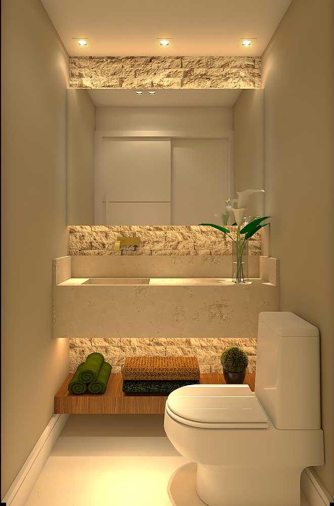 Lavabo decorado pequeno com espelho grande; destaque para a parede com revestimento de pedra