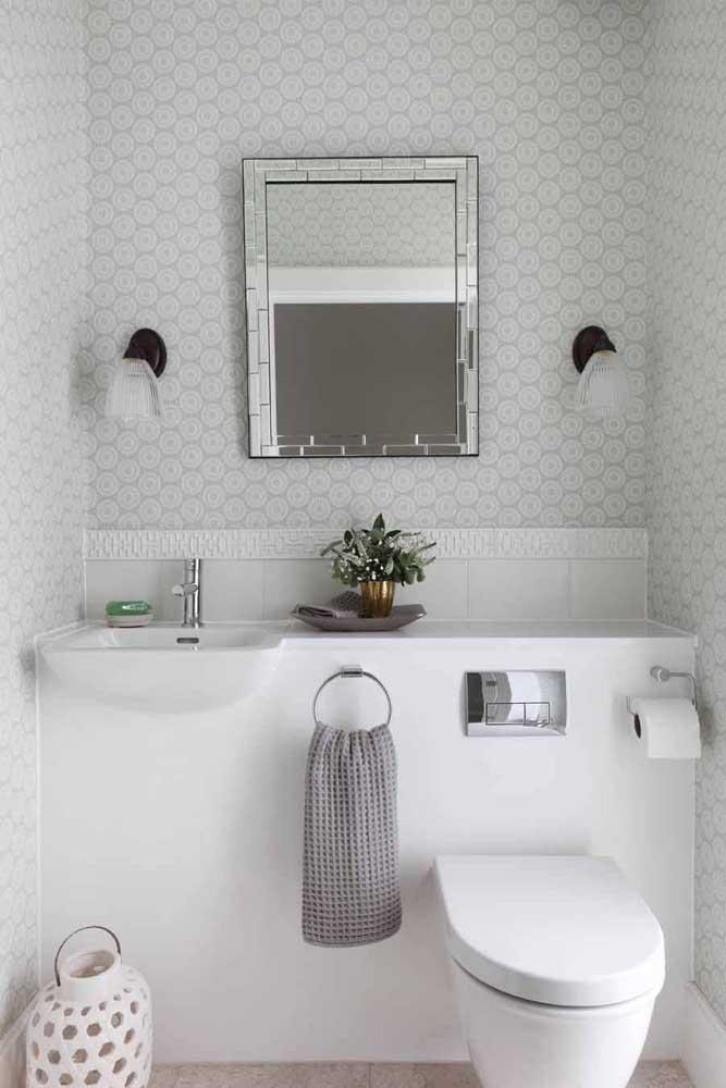 Lavabo decorado pequeno em tons claros, com itens instalados para tornar o ambiente ainda mais organizado e funcional