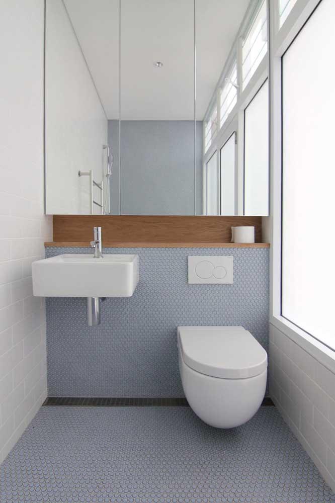 Lavabo decorado pequeno e simples, com espelheira e entrada de luz natural graças às grandes janelas do ambiente