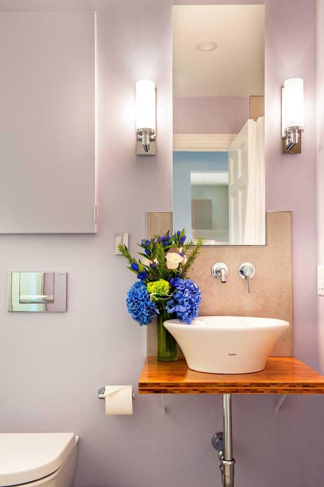 O balcão simples de madeira onde a pia está apoiada faz toda a diferença na decoração desse pequeno lavabo