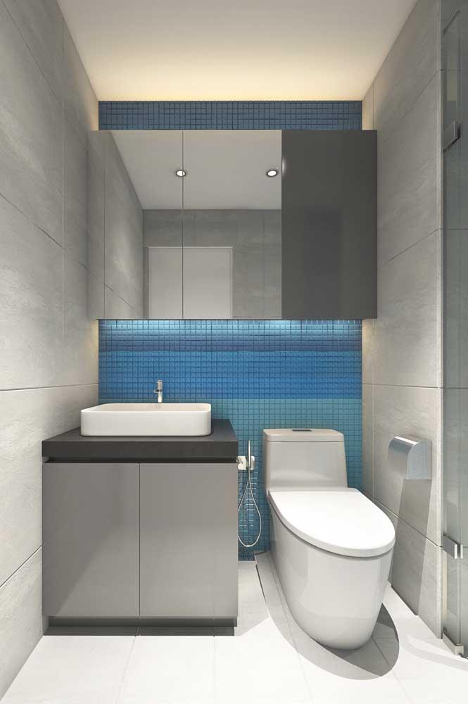Aqui, o lavabo decorado ganhou uma parede em azul para contrastar com o cinza predominante