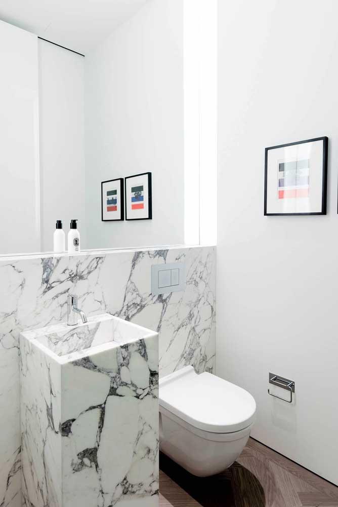 Lavabo pequeno decorado com placas de mármore e espelho por toda a parede; visual clean, mas cheio de charme
