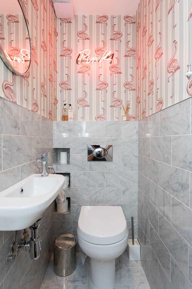 Os flamingos, ícones na decoração atual, entram nesse lavabo pela estampa do papel de parede; para fechar, um letreiro luminoso