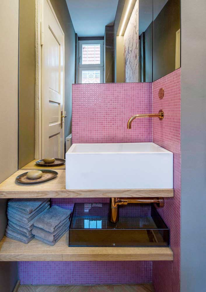 Esse lavabo apertadinho traz pastilhas cor de rosa na parede da bancada da pia