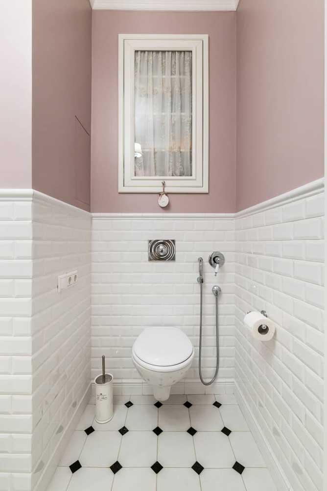 Lavabo decorado com meia parede em azulejos de metro e a outra metade em pintura