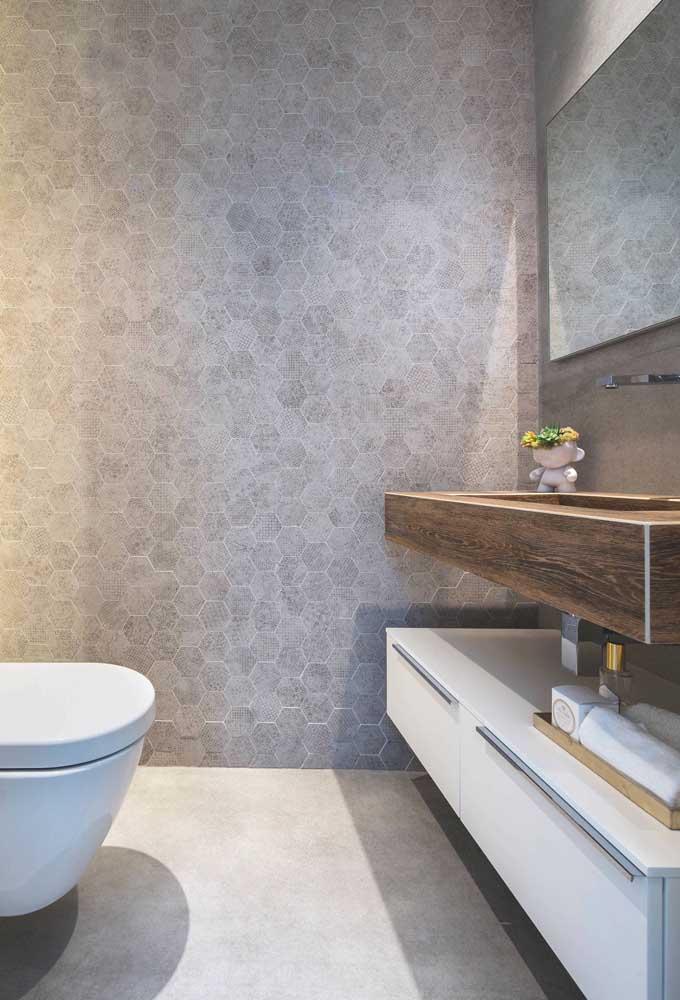 Lavabo decorado com parede de revestimento semelhante a pedras e balcão em madeira