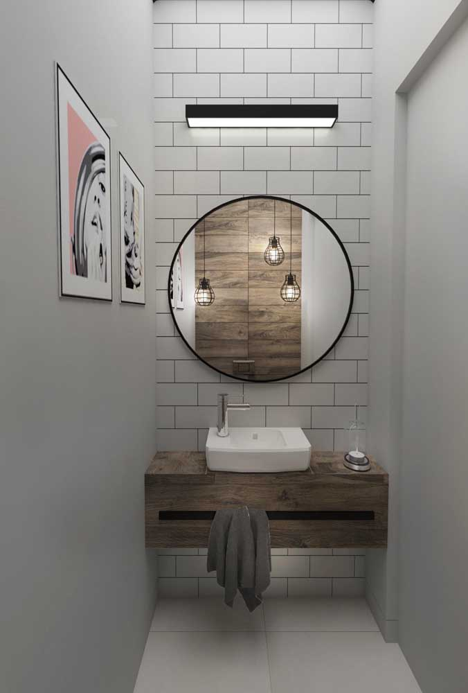 Lavabo pequeno, moderno e clean com espelho redondo para arrematar a decor