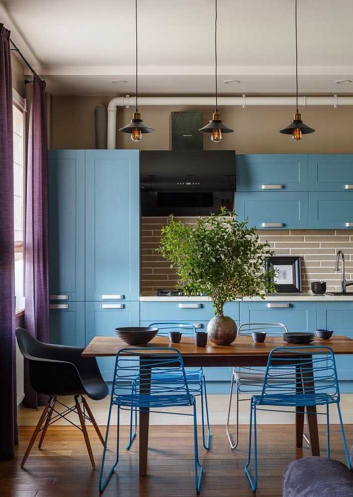 Azulejos retangulares entre a bancada e o armário da cozinha que seguem a mesma tonalidade da parede.