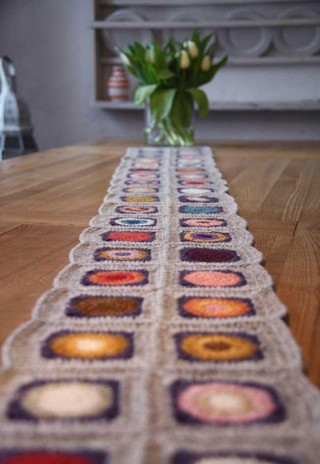 Flores de crochê unidas pelo caminho de mesa