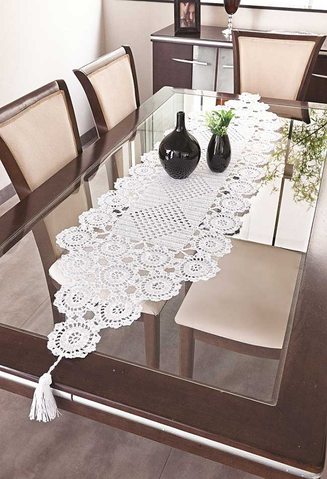 Mesa de jantar com caminho de crochê e vasos