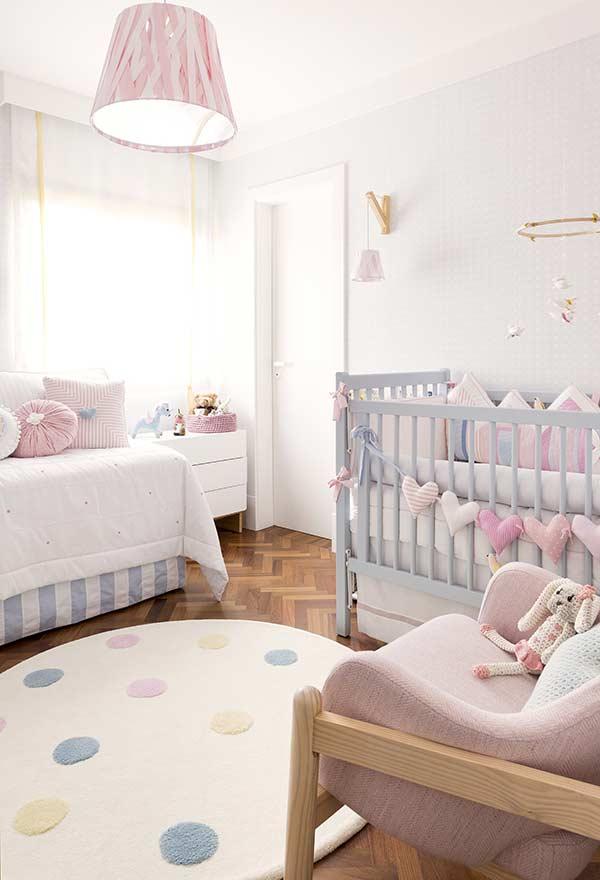 Tons claros de azul e rosa em quarto de bebê pequeno