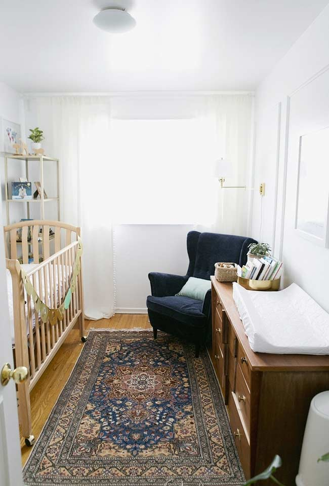 Quarto de bebê pequeno com um ar mais sofisticado e tapete tipo persa.