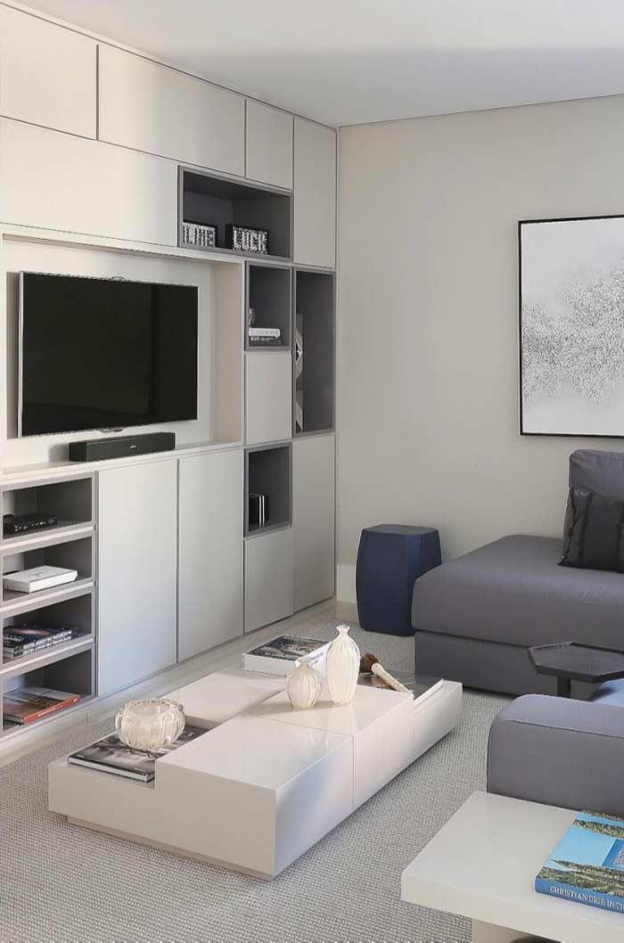 Painel junto a nichos e armários na sala de TV