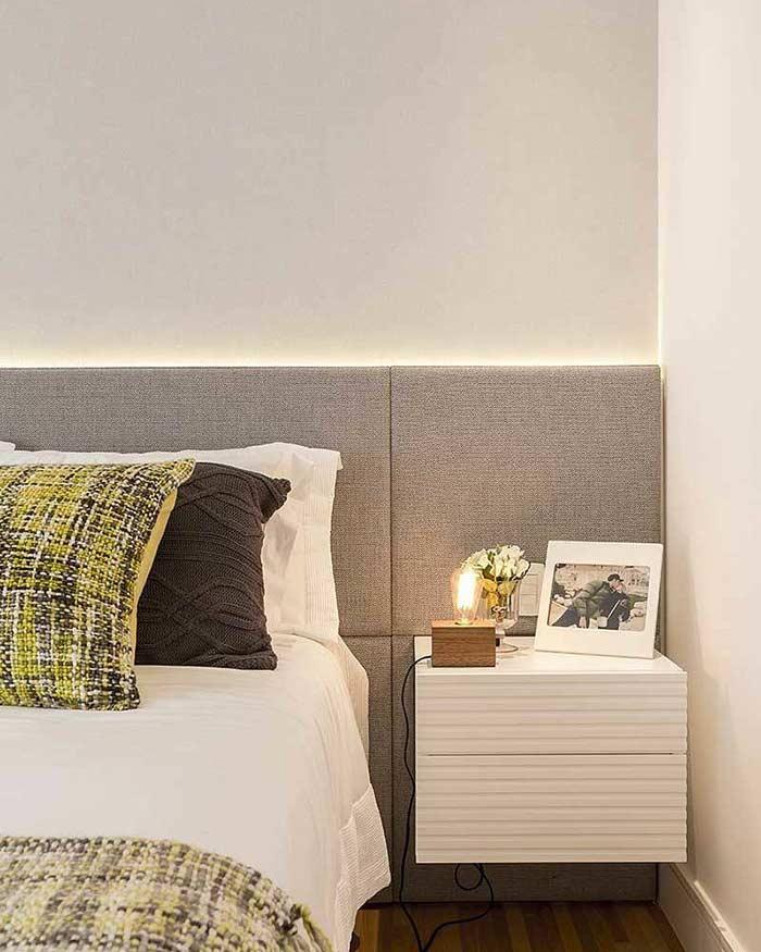 Decoração de quarto com cabeceira estofada e criado-mudo suspenso