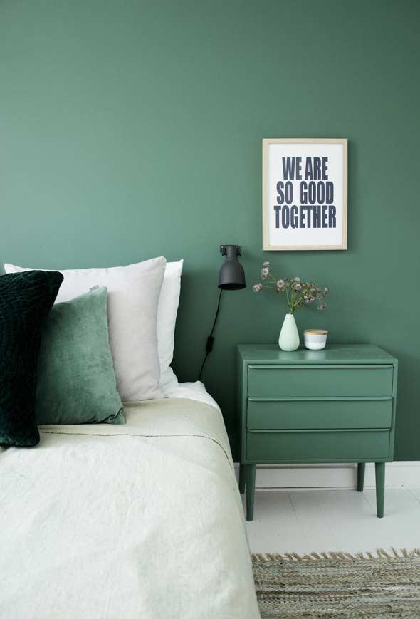 Quarto com parede verde e criado-mudo que segue a mesma cor