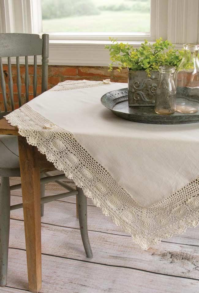 Com barrado de crochê disposta sobre mesa retangular