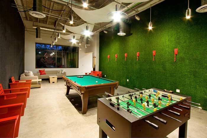 Grama sintética na parede da sala de jogos para um clima mais recreativo