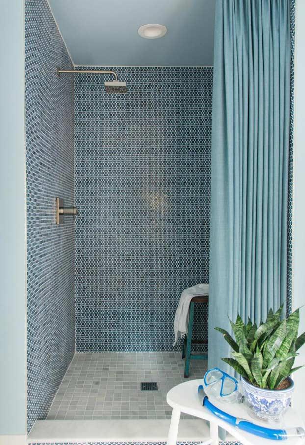 Banheiro azul com mistura de materiais e revestimentos