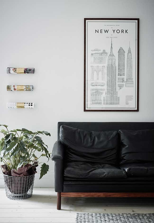 Sofá de couro com apoio e pés de madeira escura
