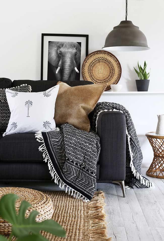 Sofá preto decorado com almofadas e manta cinza