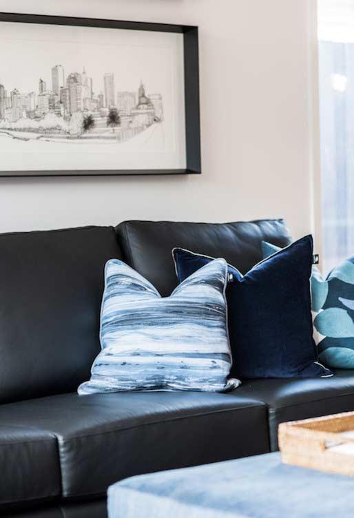 Sofá preto com almofadas estampadas
