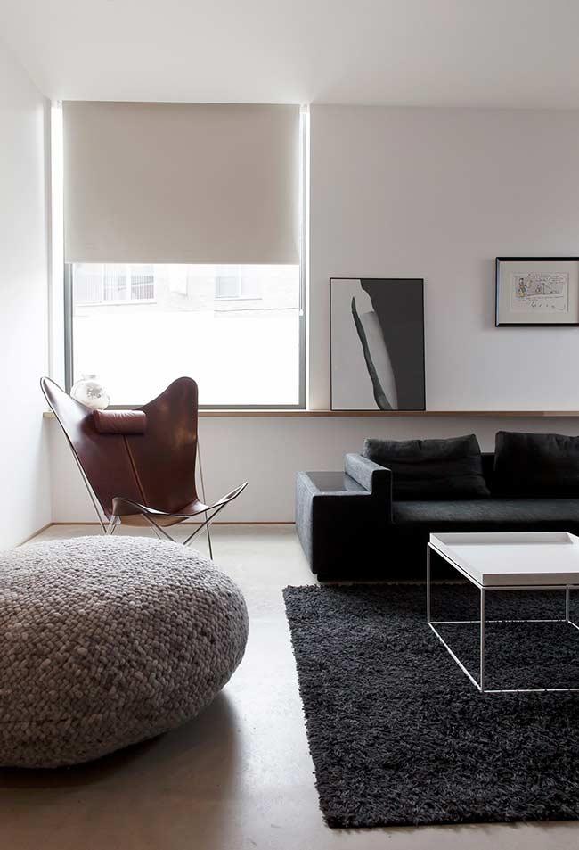Sala minimalist com sofá preto