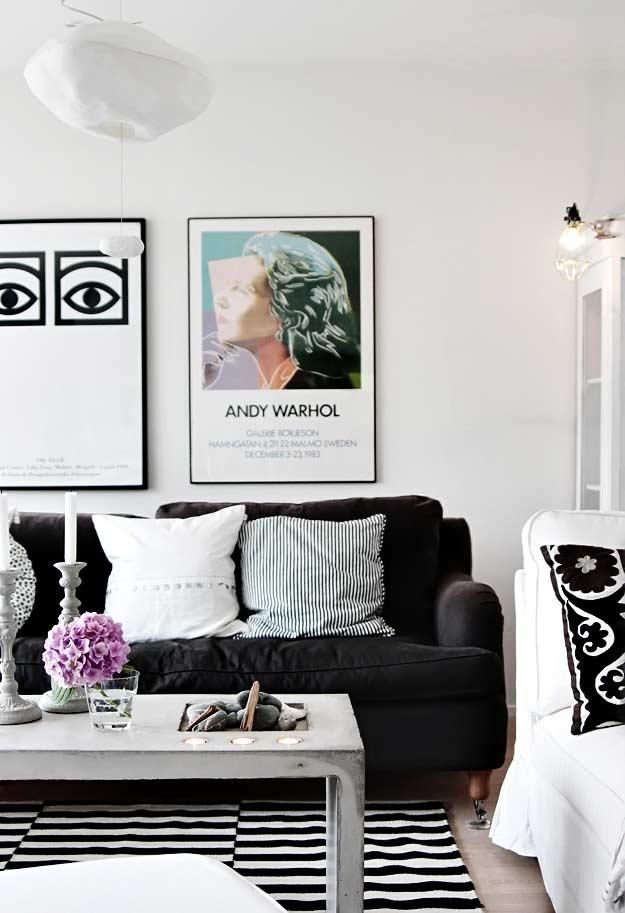 mistura de elementos mais clássicos no ambiente com um sofá preto e cheio de almofadas