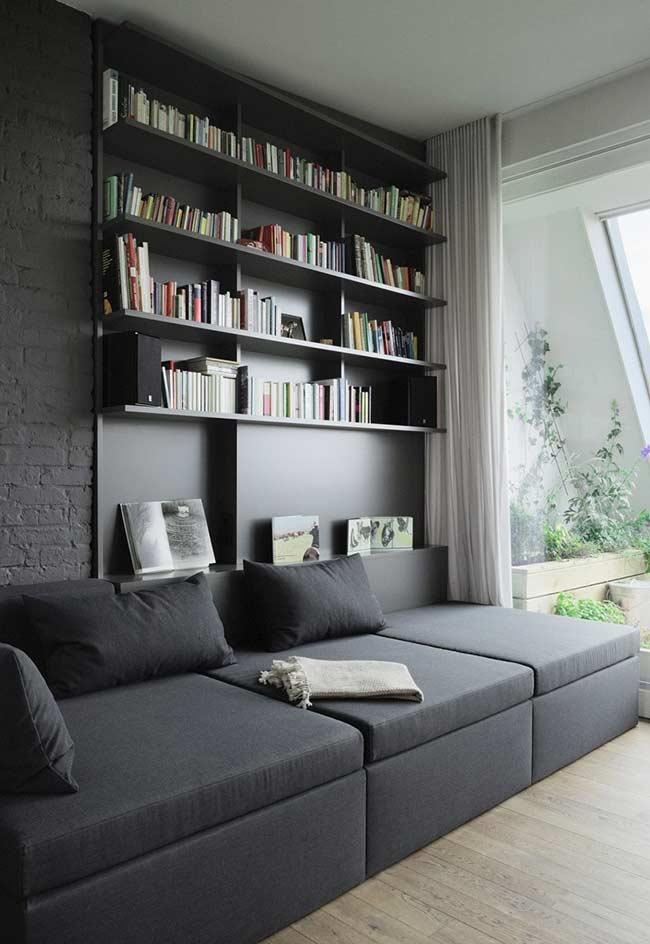 Sofá interligado ao painel com prateleiras para livros e decorações