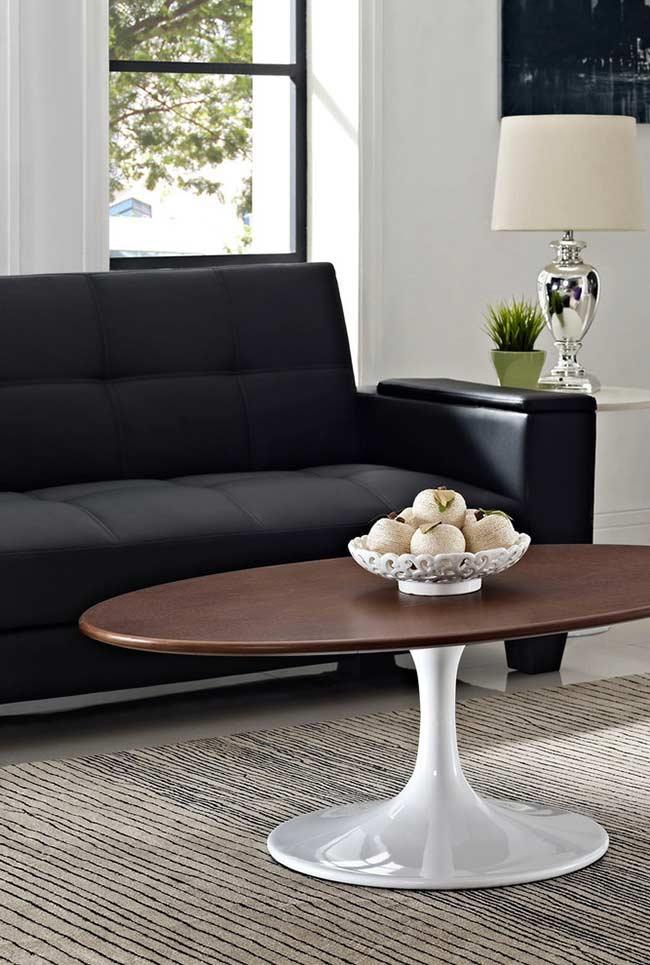Ambiente com sofá preto e elementos naturais