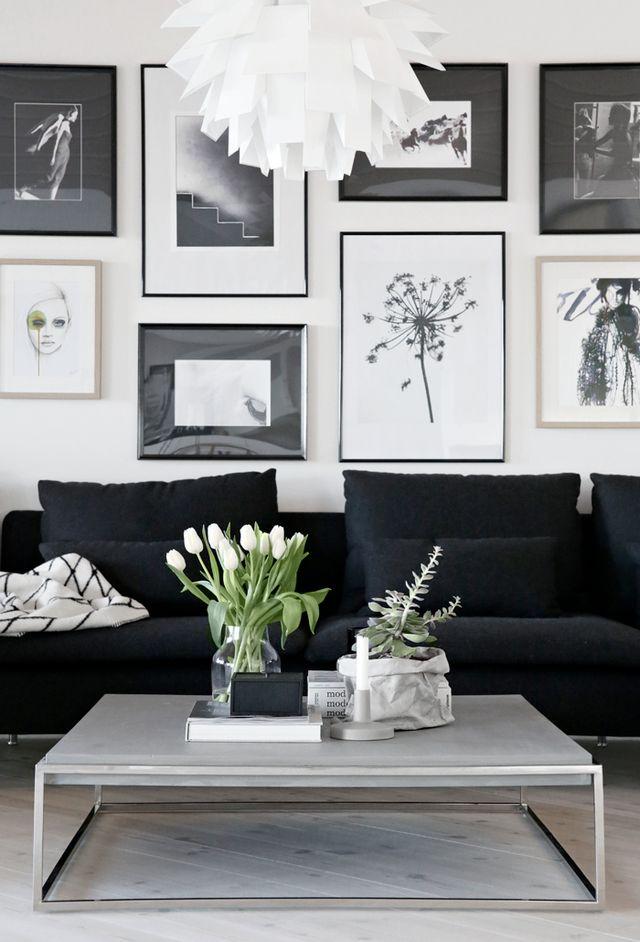 Sofá modulado preto numa decoração mais cheia e um toque final de verde