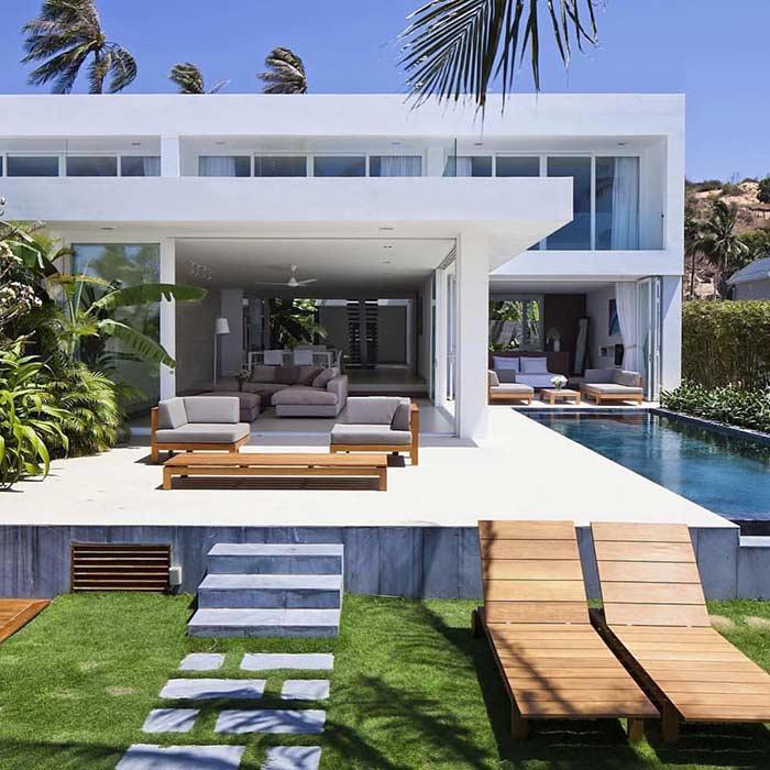 Casa com ampla área de lazer, sofás confortáveis, espreguiçadeiras e piscina com borda infinita