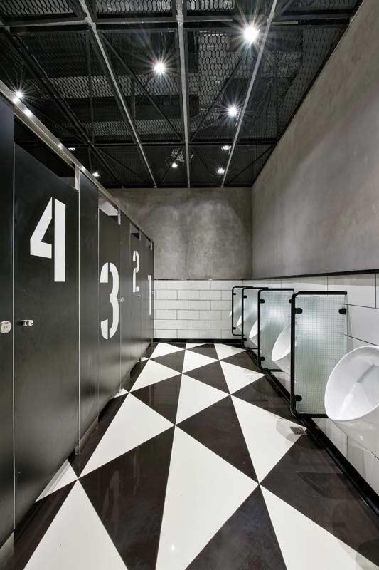 Banheiro masculino coletivo com decoração no estilo industrial