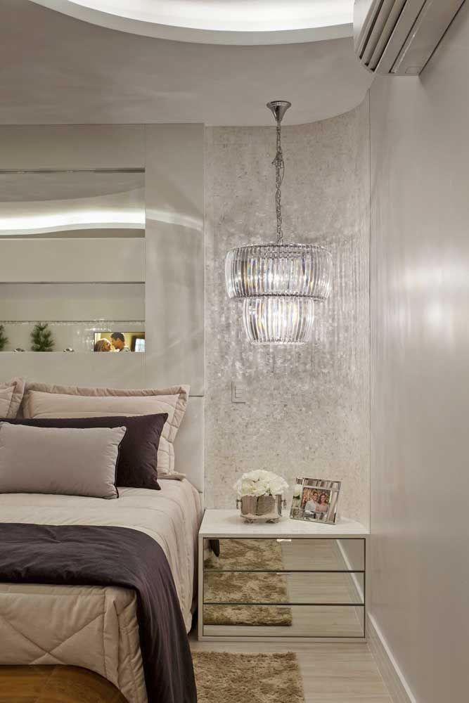Nesse quarto, o criado-mudo espelhado toma toda a faixa de parede que sobra da cama