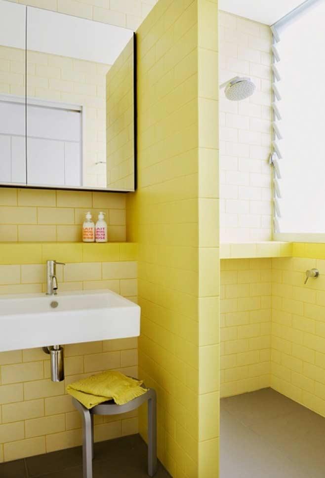 Tons de amarelo claro no revestimento do banheiro