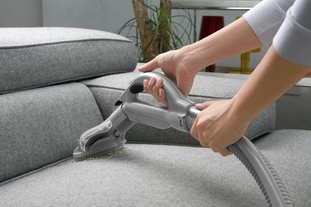 Aspirador no sofá de tecido