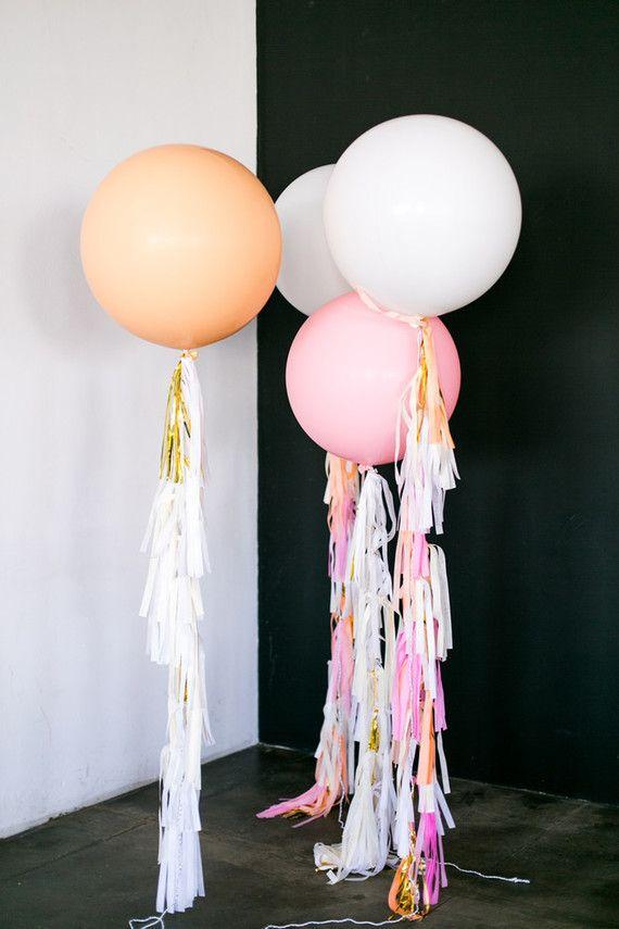 Balões presos no chão com fitinhas coloridas