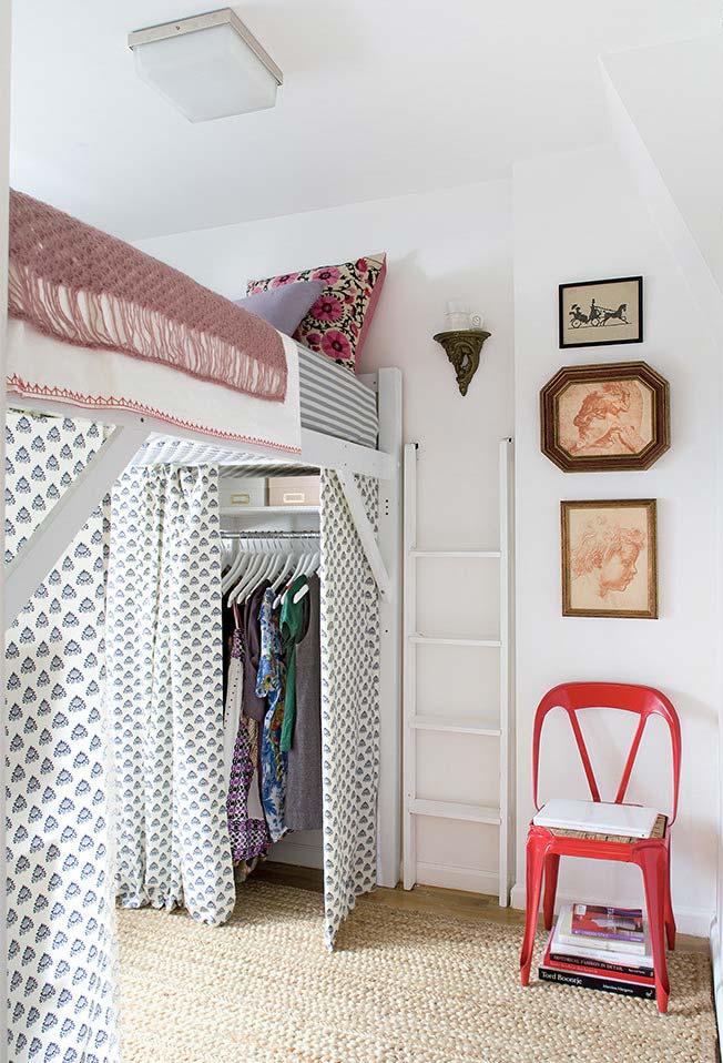 Cama na parte de cima com escada fixada na parede e closet na parte de baixo no quarto pequeno