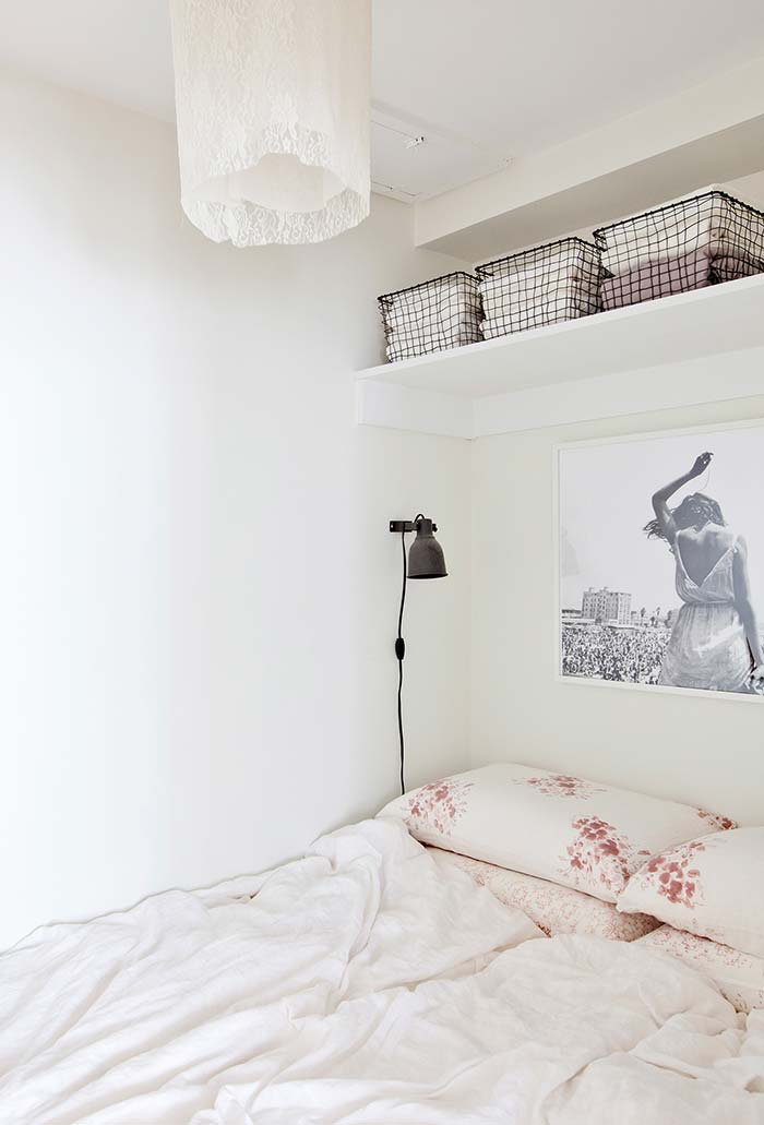 Prateleira alta com cestas de metal para quarto pequeno