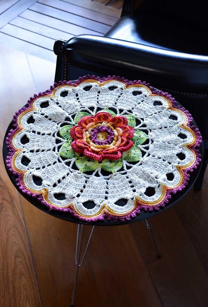 Em uma mesa redondo você pode colocar um centro de mesa de crochê com formato de flor no meio.