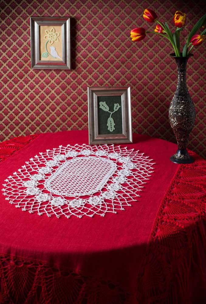 O centro de mesa de crochê na cor branca faz um perfeito contraste com a toalha de mesa na cor vermelha.