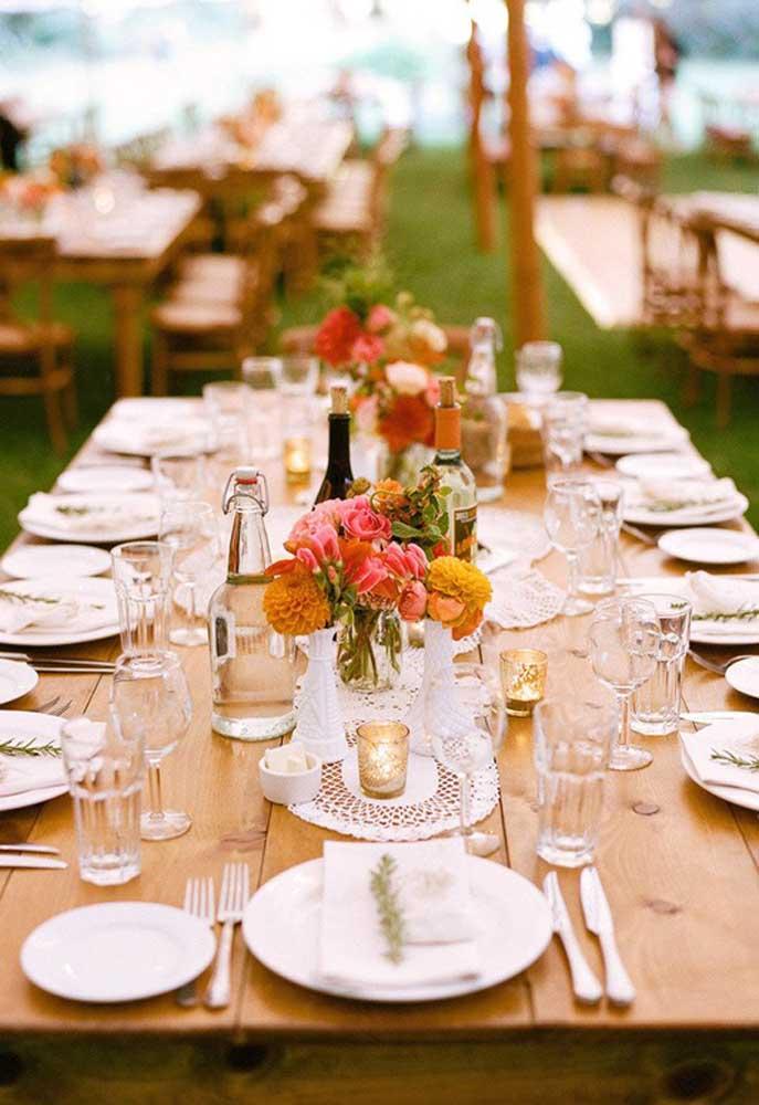 Em cima do centro de mesa coloque os vasos de flores para decorar.