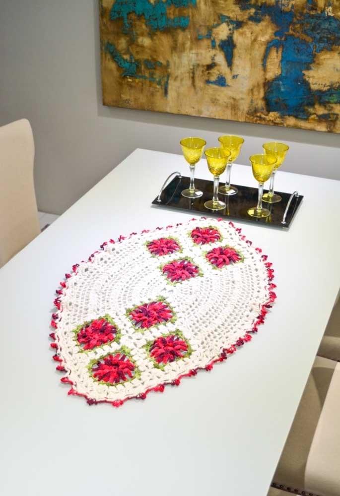 O centro de mesa no formato oval destaca a mesa de jantar.