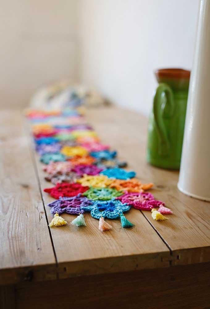 O centro de mesa de crochê feito com linhas coloridas deixa o ambiente mais cool.