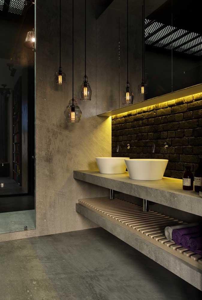Faixa de parede de tijolinhos de demolição para o banheiro; repare como o material completa o estilo despojado do ambiente que ficou ainda mais valorizado pela iluminação indireta